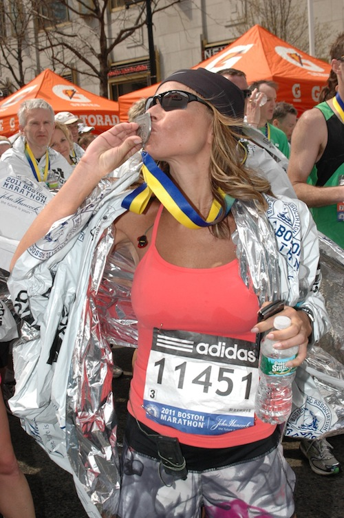 Catherine kissing the medal at the 2011 Boston Marathon